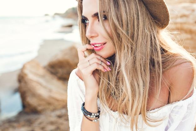 人けのないビーチで長い髪を持つ魅力的なブロンドの女の子のクローズアップの肖像画。彼女は唇に指を付けたまま、遠くを見ています。