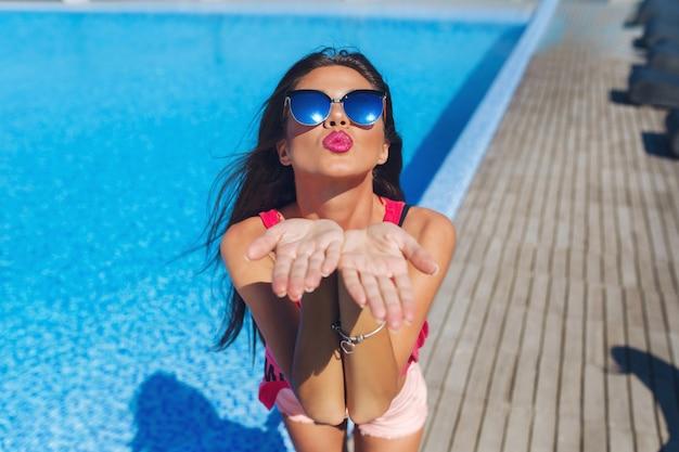 プールの近くに立っている長い髪の魅力的なブルネットの少女のクローズアップの肖像画。彼女はカメラに手を伸ばしてキスをします。