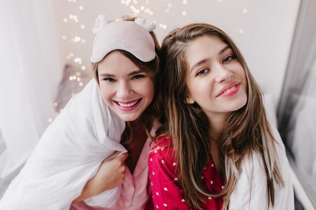 寝室で喜んでポーズをとるパジャマ姿の魅力的な白人女性のクローズアップの肖像画。白い毛布の下に座っているヨーロッパの女の子の写真。
