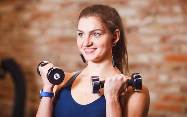 매력적인 쾌활한 sportswoman의 초상화를 닫습니다. 벽돌 벽의 배경에 체육관에서 아령으로 운동을하는 스포티 한 여자