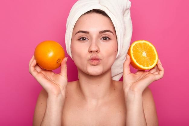 魅力的な陽気な女性のポートレートを閉じますオレンジスライスを保持、唇を折りたたみを維持、タオルと裸の肩を着て、ピンクのポーズ。スタジオでモデルのポーズ。自然の美の概念。