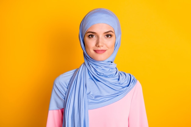 밝은 노란색 배경 위에 격리된 파란색 히잡을 쓰고 있는 매력적인 쾌활한 겸손한 이슬람교도의 클로즈업 초상화