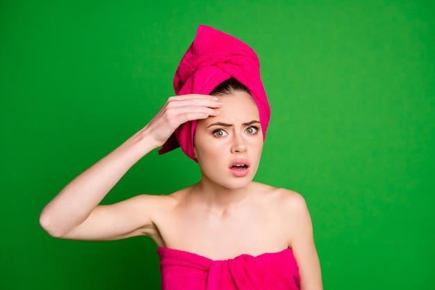 鮮やかな緑色の背景で隔離の額の脂性肌に触れる頭にタオルターバンを身に着けている魅力的な失望した女性のクローズアップの肖像画