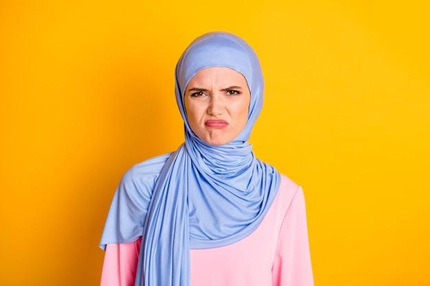 히잡을 쓴 매력적인 변덕스러운 이슬람교도의 클로즈업 초상화는 밝은 노란색 배경에 격리된 입술을 추구합니다