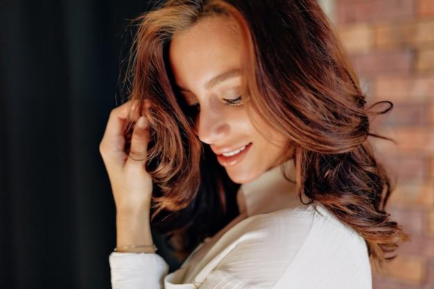 黒い壁にポーズをとって笑っている巻き毛の魅力的なヨーロッパの女性の肖像画をクローズアップ