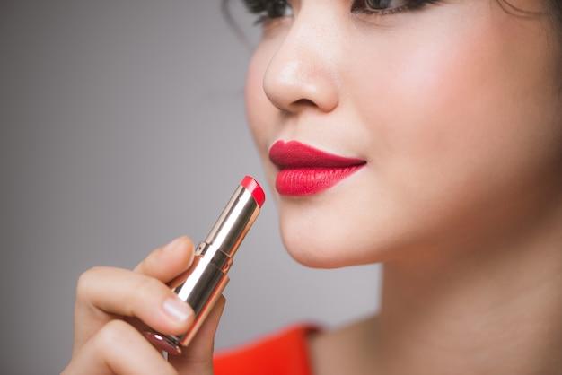 Крупным планом портрет привлекательной девушки, держащей красную помаду на сером фоне