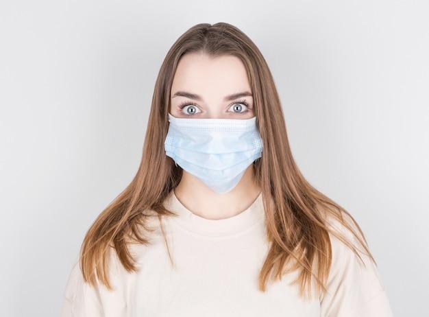매력적인 여자의 클로즈 업 초상화는 독감이나 감기로부터 보호하기 위해 얼굴 마스크를 착용, 흰색 배경 위에 절연