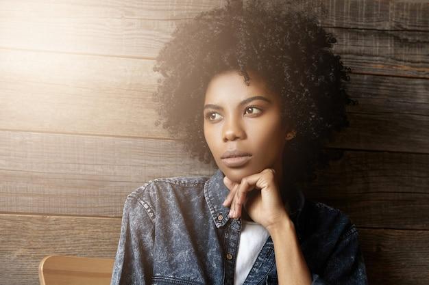 カーリーのヘアカットと魅力的な見栄えの良い若いアフリカ女性のポートレートを閉じます