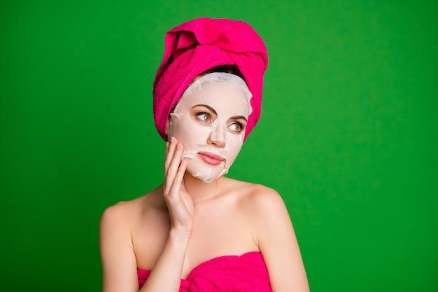 밝은 녹색 배경에 격리된 순수한 피부를 만지는 안면 마스크를 쓴 터번을 쓴 매력적인 건강한 여성의 클로즈업 초상화