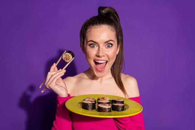 スティックで寿司を食べる魅力的な空腹の陽気な女の子のクローズアップの肖像画孤立した明るい紫紫の色の背景