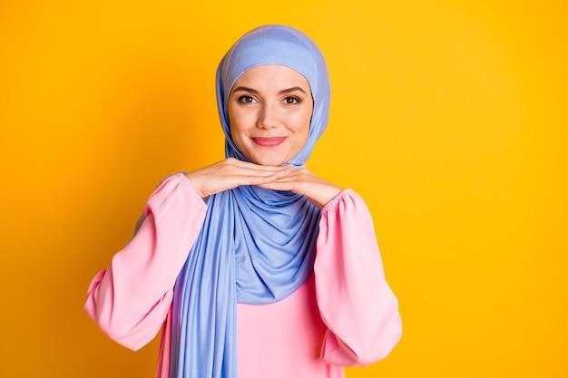 밝은 노란색 배경 위에 격리된 포즈로 히잡을 쓴 매력적이고 쾌활한 이슬람 여성의 클로즈업 초상화