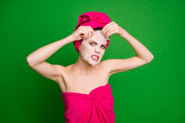 明るい緑色の背景に分離された顔のマスクを脱いでターバンを身に着けている魅力的な裸の裸の狂った怒りのイライラした女性のクローズアップの肖像画