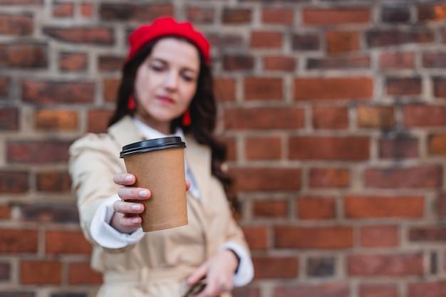 赤レンガで隔離の紙カップコーヒーで保持している魅力的なかなりスタイリッシュな陽気な縮れ毛のブルネットの少女のクローズアップの肖像画、屋外で歩く幸せな女性。