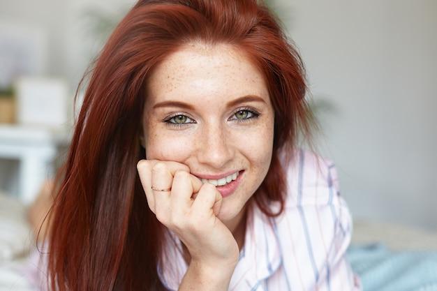 緑の目と完璧なそばかすのある肌を持つ魅力的な赤い髪の若い白人女性の肖像画をクローズアップして、パジャマを着て朝ベッドで過ごします。美容、若さ、レジャー、人、ライフスタイル