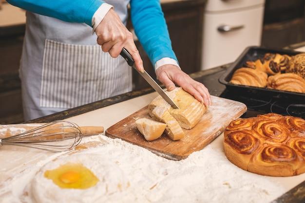 Портрет конца-вверх привлекательной старшей постаретой женщины варит на кухне. бабушка делает вкусную выпечку.