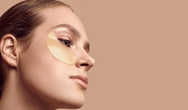 Макро портрет привлекательной чувственной девушки с обнаженными плечами, применяя патчи на ее лице на фоне студии