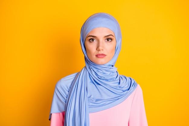 밝은 노란색 배경 위에 격리된 파란색 파스텔 히잡을 쓰고 있는 매력적인 진지한 이슬람교도의 클로즈업 초상화