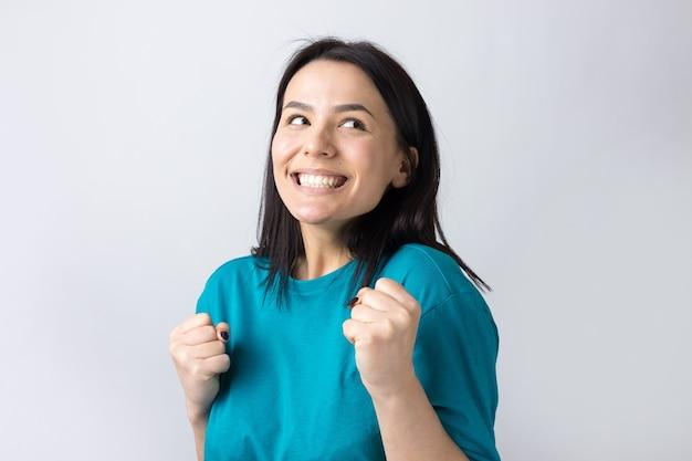 灰色の背景に分離されたジーンズシャツの服を着ている彼女の女の子の若い彼女の上げられた握りこぶしと笑顔で勝利の魅力的な叫びの肖像画をクローズアップ