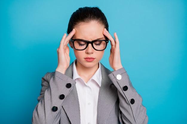 Крупным планом портрет привлекательной больной угрюмой бизнес-леди, которая плохо себя чувствует, трогая храмы, изолированные на ярко-синем цветном фоне