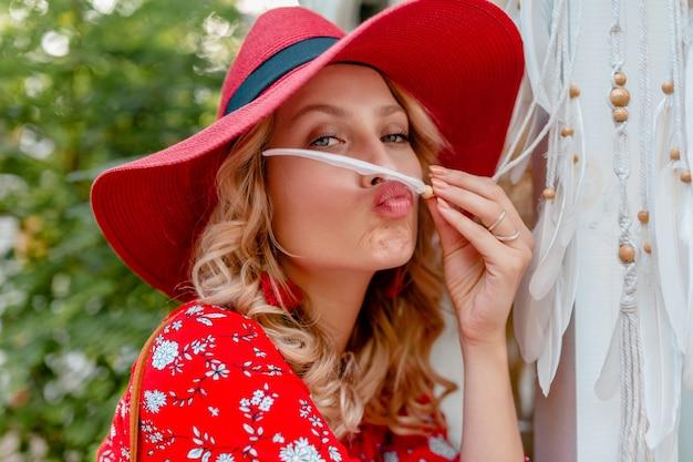 흰색 깃털 섹시 관능적 인 얼굴 피부를 들고 밀짚 빨간 모자와 블라우스 여름 패션 복장에 매력적인 세련된 금발 웃는 여자의 클로즈 업 초상화