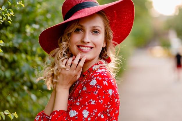 わらの赤い帽子とブラウスの夏のファッションの衣装で笑顔の巻き毛の髪型で魅力的なスタイリッシュな金髪の笑顔の女性のクローズアップの肖像画