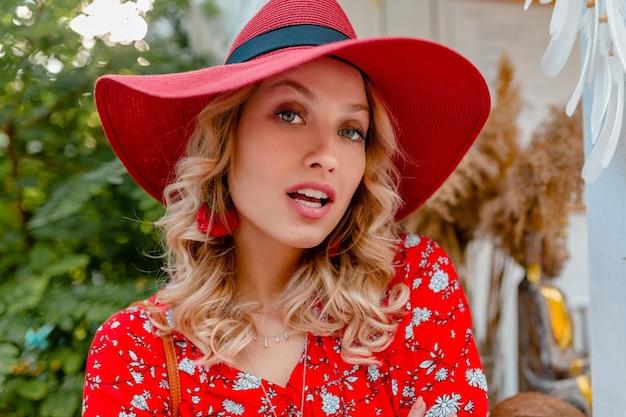 Крупным планом портрет привлекательной стильной блондинки улыбается женщина в соломенной красной шляпе и блузке летней моды наряд с чувственной улыбкой