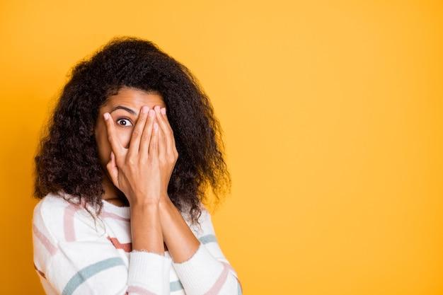 Портрет крупным планом привлекательной волнистой девушки, прячущей лицо в ладонях, шпионит за взглядом, изолированным над ярко-яркой стеной яркого желтого цвета