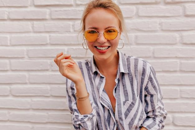 오렌지 안경과 벗겨진 셔츠를 입고 멋진 미소로 매력적인 여자의 초상화를 닫습니다