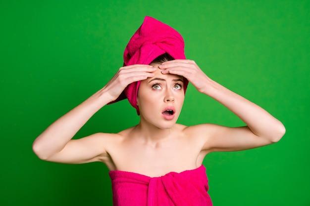 明るい緑色の背景で隔離の額に触れるターバンを身に着けている魅力的な心配している神経質な女性のクローズアップの肖像画