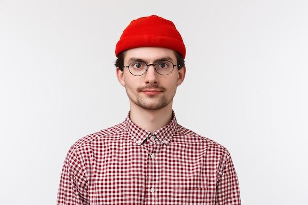 メガネと赤いビーニーのひげを生やした白人ヒップスター男のクローズアップの肖像画、チェックシャツ、カメラのカジュアルな表情、人々、ライフスタイル、感情の概念を探して