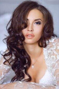美しい花嫁の肖像画を閉じます。花嫁の朝。結婚式の朝。長いウェーブのかかった髪のブルネットの少女。