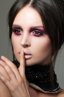 現代のファッションと美しいブルネットの女性のクローズアップの肖像画は、彼女の指でshh記号を作るを構成します。美しさ、秘密、ファッションのコンセプト。