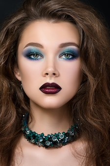 現代のファッションと美しいブルネットの女性のクローズアップの肖像画を占めています。スモーキーな目と暗い赤い唇。