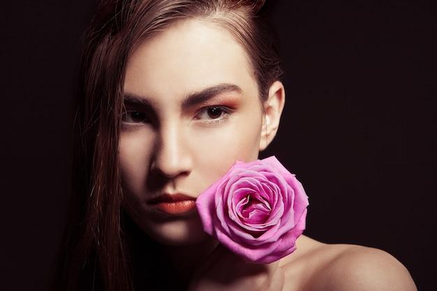 ピンクのバラと美しいブルネットの女性のクローズアップの肖像画