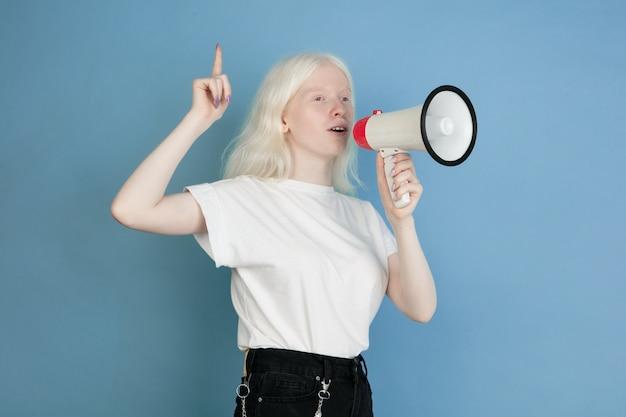 青の美しい白人アルビノの女の子の肖像画を閉じます。スタイリッシュな表情の金髪女性モデル。表情、人間の感情、子供時代、広告、販売、多様性の概念。