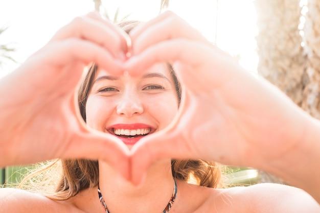 美しいの肖像画をクローズアップ。カメラで手で愛の囲炉裏サインをしている白人の若い女性-太陽の明るい背景と楽しい幸せの人々の概念
