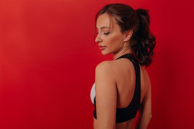 赤い壁に分離されたスポーツトップを身に着けている美しい黒髪の女性の肖像画をクローズアップ