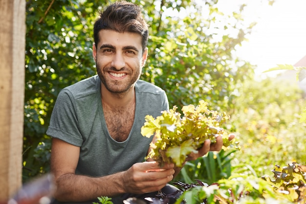 웃고, 정원에서 일하고, 상추 잎을 수집하고, 그의 집에서 친구들과 저녁 모임을 준비하는 아름다운 어두운 피부 수염 백인 농부의 초상화를 닫습니다.