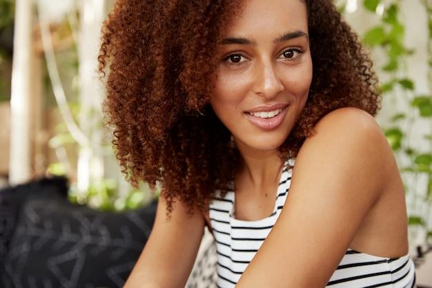 Крупным планом портрет красивой темнокожей женщины с афро-прической имеет уверенный веселый вид, свободное время проводит в кафетерии. хорошо выглядящая молодая афро-американская женщина воссоздает после работы