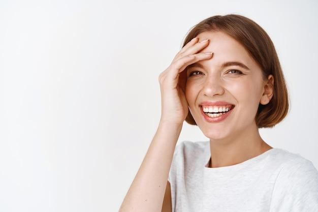 짧은 머리를 가진 아름다운 여성 모델의 클로즈업 초상화, 웃고 근심 걱정 없이 웃고, 흥분한 얼굴을 만지고, 흰 벽에 기대어