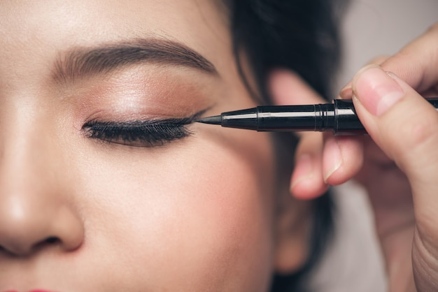 目を閉じて彼女のまぶたに黒いアイライナーに触れている美しい少女のクローズアップの肖像画。