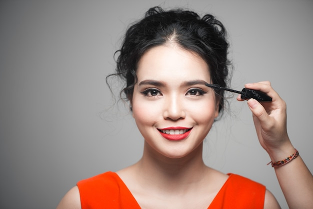 Крупным планом портрет красивой девушки, касающейся черной туши для ресниц