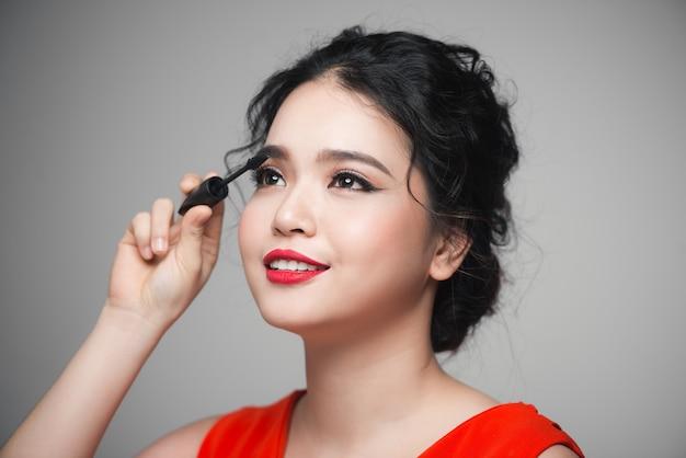 검은 마스카라를 속눈썹에 만지는 아름다운 소녀의 클로즈업 초상화