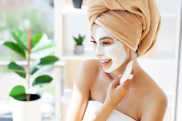 Макро портрет красивой девушки с полотенцем на голове, применяя маску для лица.