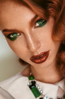 そばかすと緑の目を持つ美しい少女の肖像画をクローズアップ