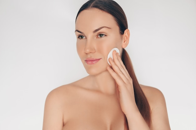 Закройте вверх по портрету красивой половинной нагой естественной женщины красоты очищая совершенную кожу стороны изолированную кожей белую стену. уборка лечебных процедур. концепция спа по уходу за кожей.