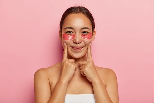 아름다운 한국 여성의 초상화를 닫고 붓기를 위해 눈 아래에 화장품 패치를 착용하고 뺨에 검지 손가락을 유지하고 부드럽게 미소를 짓고 셔츠가없는 포즈를 취하며 얼굴에 다크 서클과 주름을 피합니다.