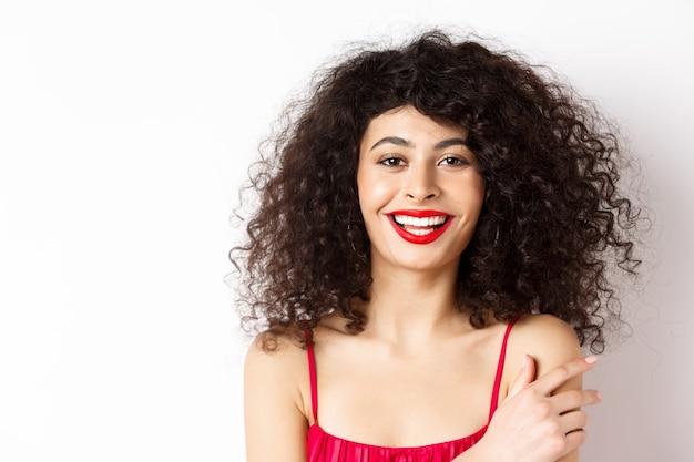 巻き毛と赤い唇、笑顔と幸せな笑い、白い背景の上に立っている美しい女性のクローズアップの肖像画。