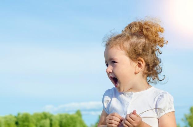 美しい少女、幸せな子供の肖像画を間近します。屋外の青い空に肯定的な子供、笑顔します。