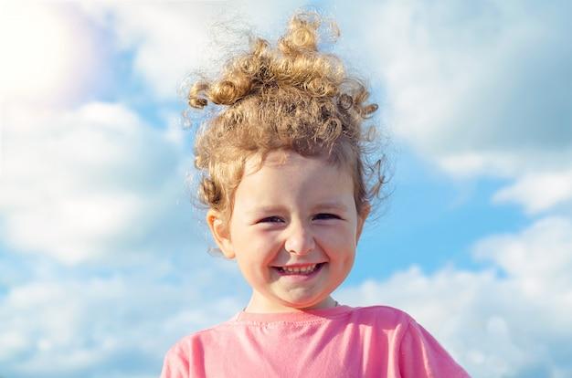美しい少女、幸せな子供の肖像画を間近します。屋外の肯定的な子供
